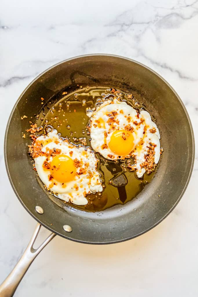 A frying pan with two fried eggs in chili crunch oil.