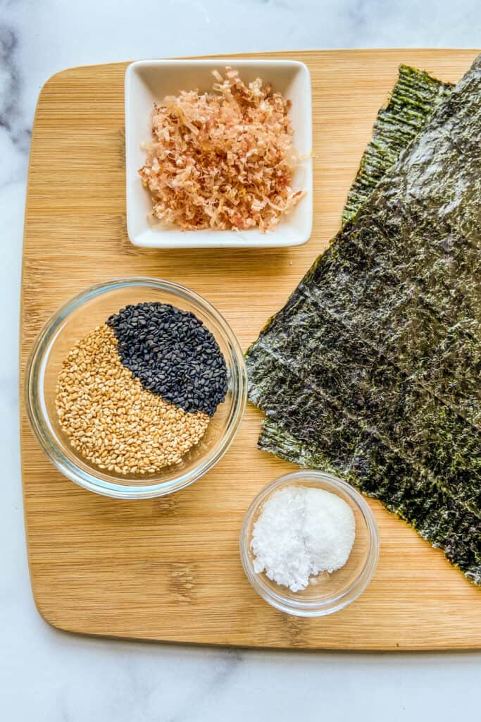 Two nori sheets, a bowl of bonita flakes, a bowl of black and white sesame seeds, and a bowl of salt and sugar on a cutting board.