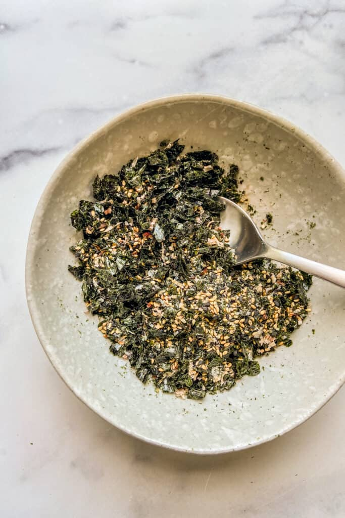 An overhead shot of a bowl of furikake seasoning with a spoon.