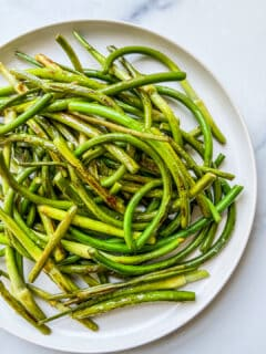An overhead shot of a plate of cooked scapes.