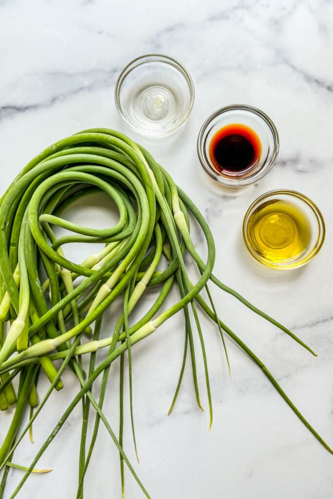 Garlic scapes, a bowl of rice wine vinegar, a bowl of soy sauce, and a bowl of olive oil.