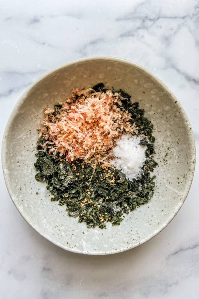 A bowl of crushed nori and sesame seeds with bonita flakes, salt, and sugar on top.