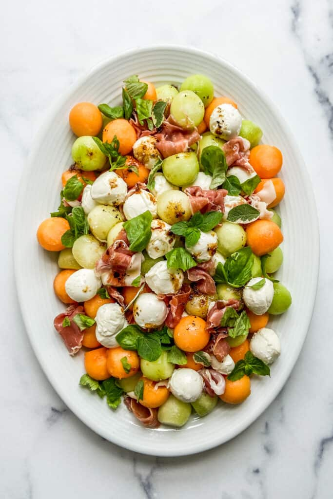 An overhead shot of an oval plate of melon prosciutto salad.