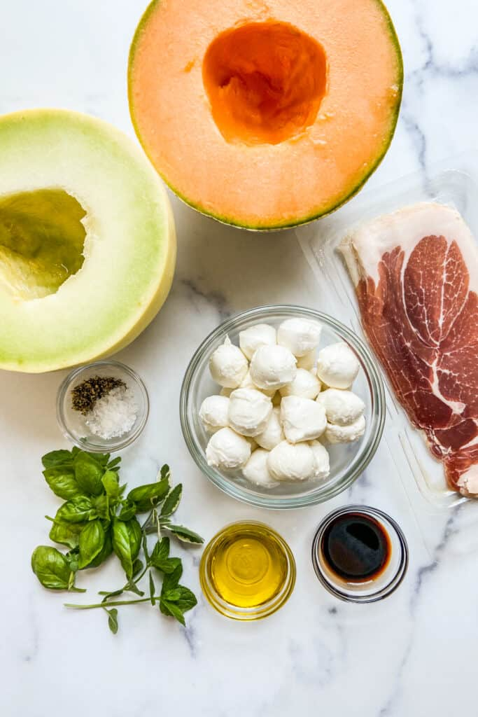 A halved cantaloupe, a halved honeydew, prosciutto, mozzarella balls, fresh herbs, salt, pepper, olive oil, and balsamic.