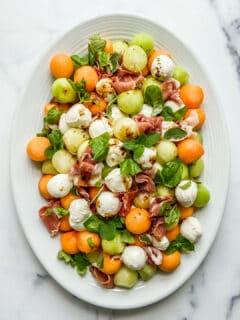 Melon and prosciutto salad on a white serving dish.