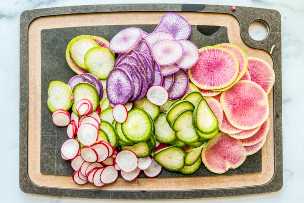 Sliced radishes on a cutting board.
