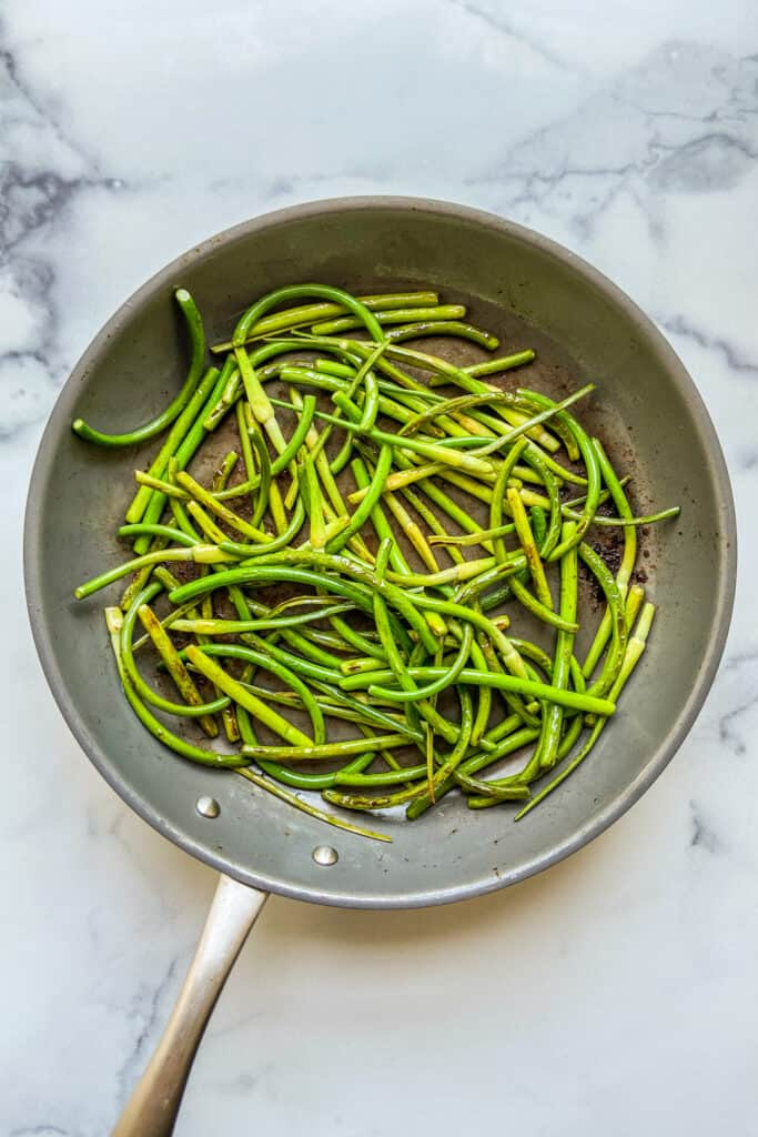Cooked garlic scapes in a frying pan.