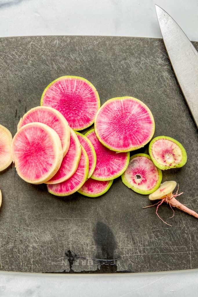 Slices of watermelon radish on a black cutting board.