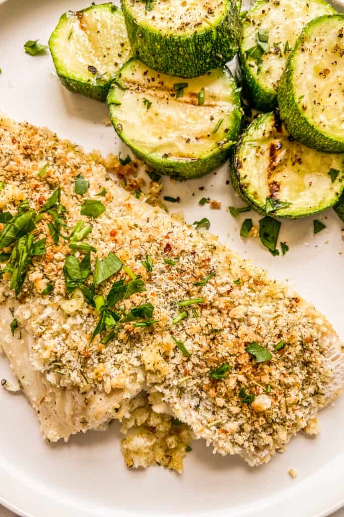 A closeup shot of crispy haddock fillets next to grilled zucchini.