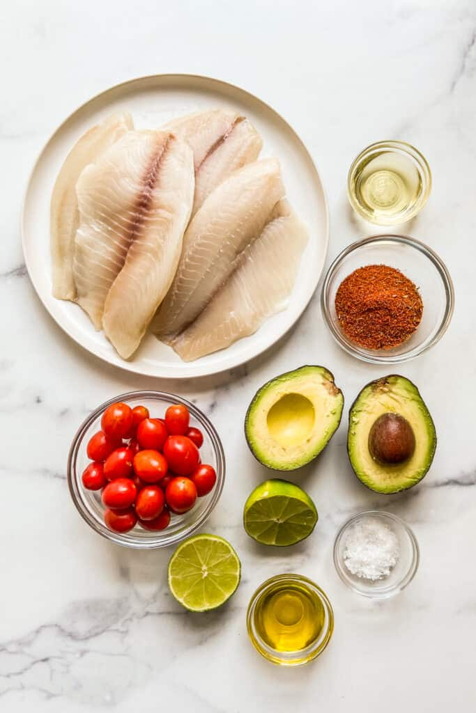 Tilapia fillets, blackening seasoning, an avocado, cherry tomatoes, lime, sea salt, and oil on a marble background.