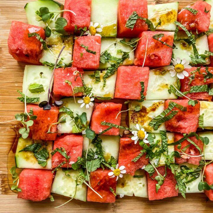 A cucumber watermelon mosaic salad on a cutting board.