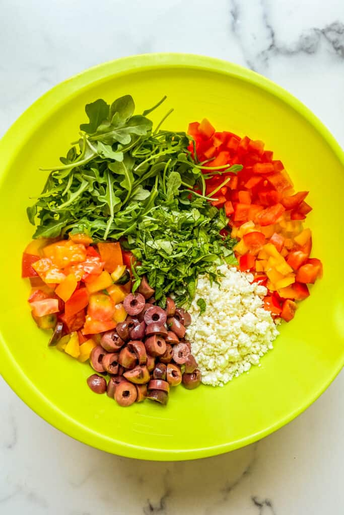 Arugula, chopped bell pepper, chopped olive, chopped tomatoes, and feta in a large green mixing bowl.