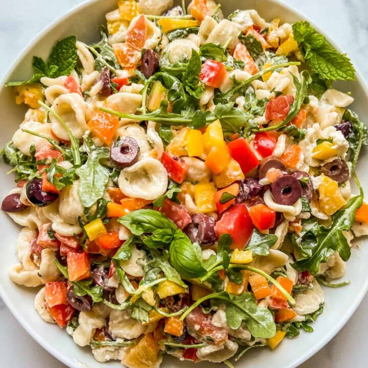 A Mediterranean pasta salad in a large white serving bowl.