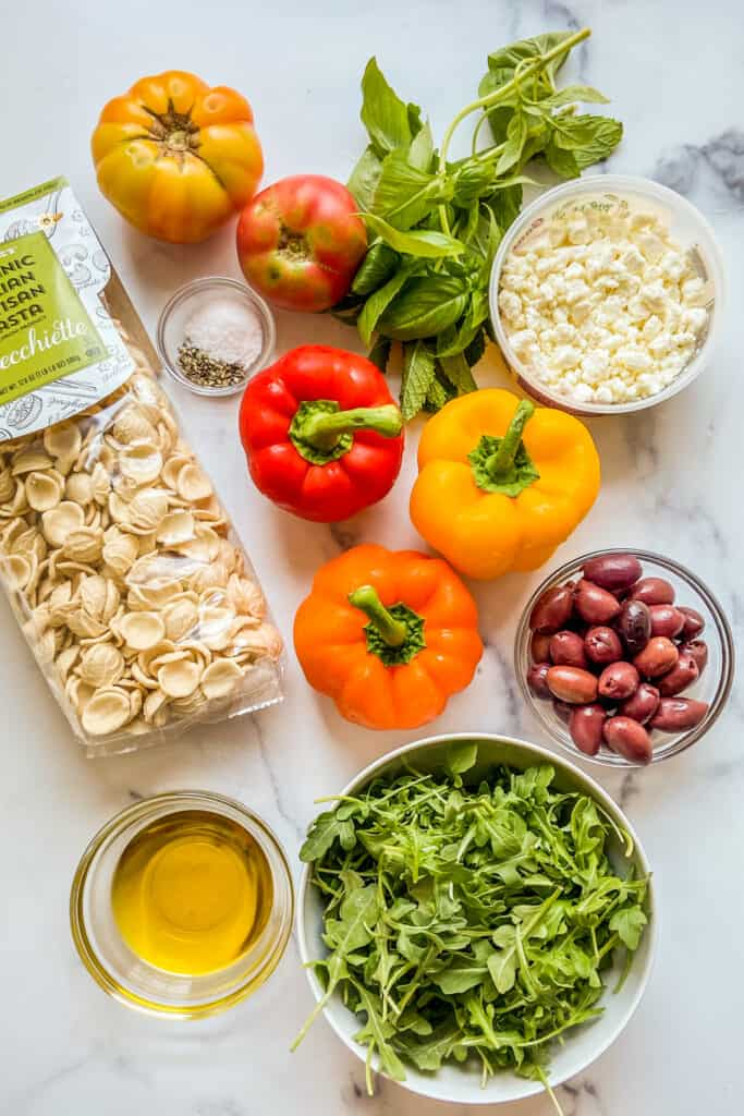Bell peppers, tomatoes, a bag of pasta, olives, feta, arugula, fresh herbs, and olive oil on a marble background.