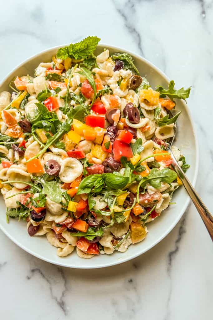 A pasta salad with bell peppers, olives, and arugula in a large white serving bowl.