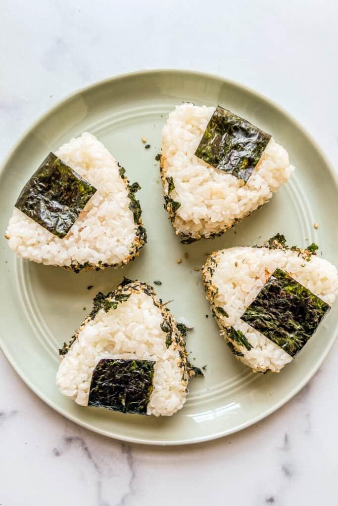 Four spicy tuna onigiri sitting on a green plate.