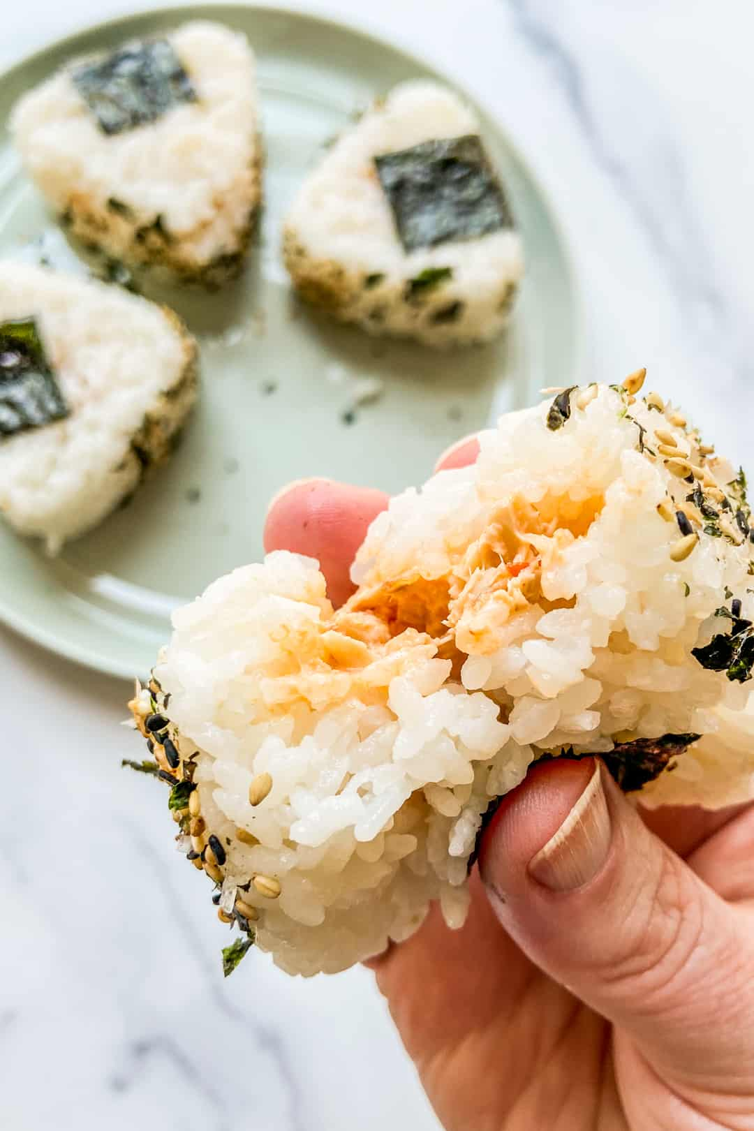 A hand holding an onigiri with a bite taken out of it.