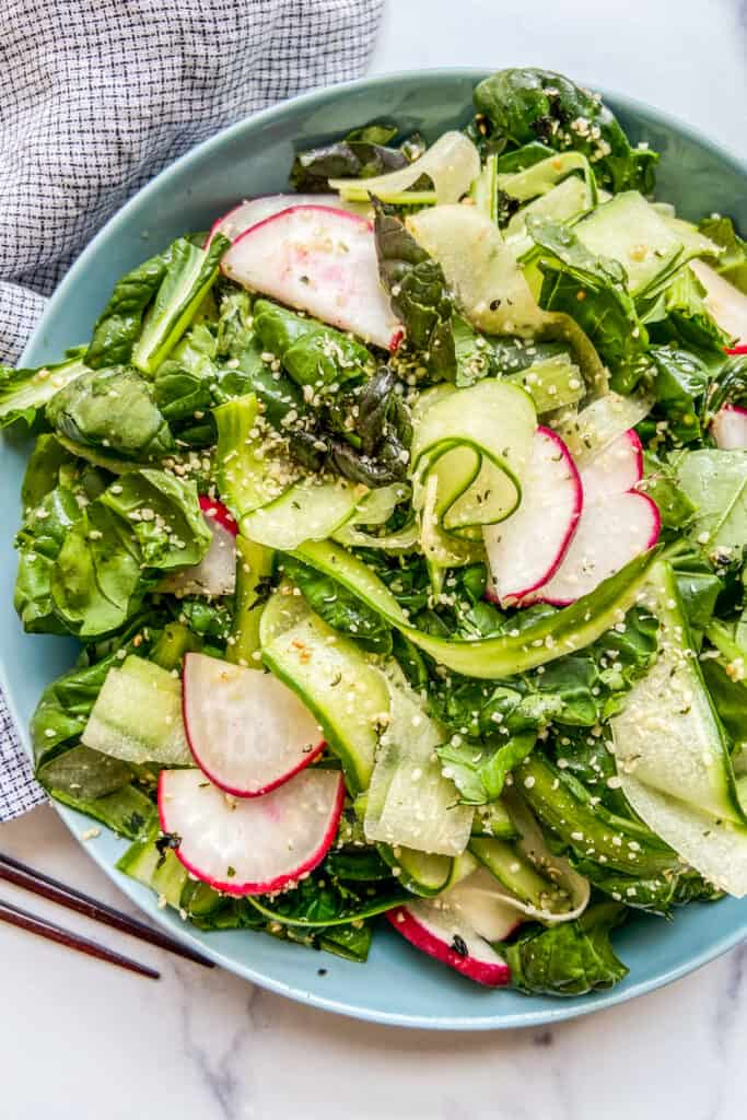 Tatsoi greens salad in a blue serving bowl next to a napkin and chopsticks.