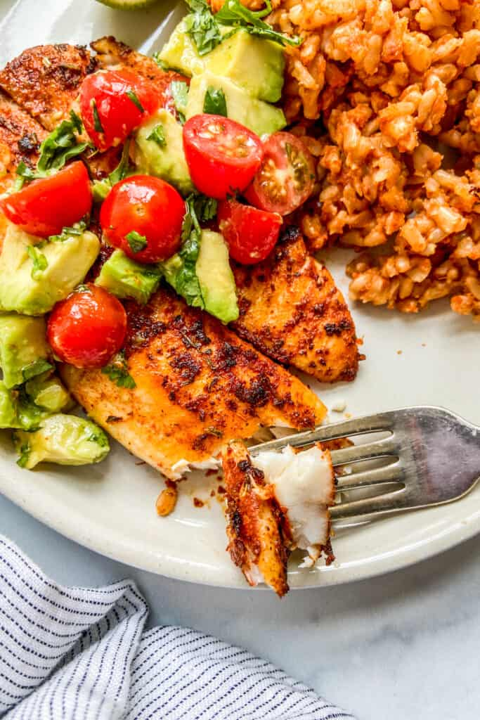 Blackened tilapia on a plate, topped with tomatoes and avocado, next to rice.