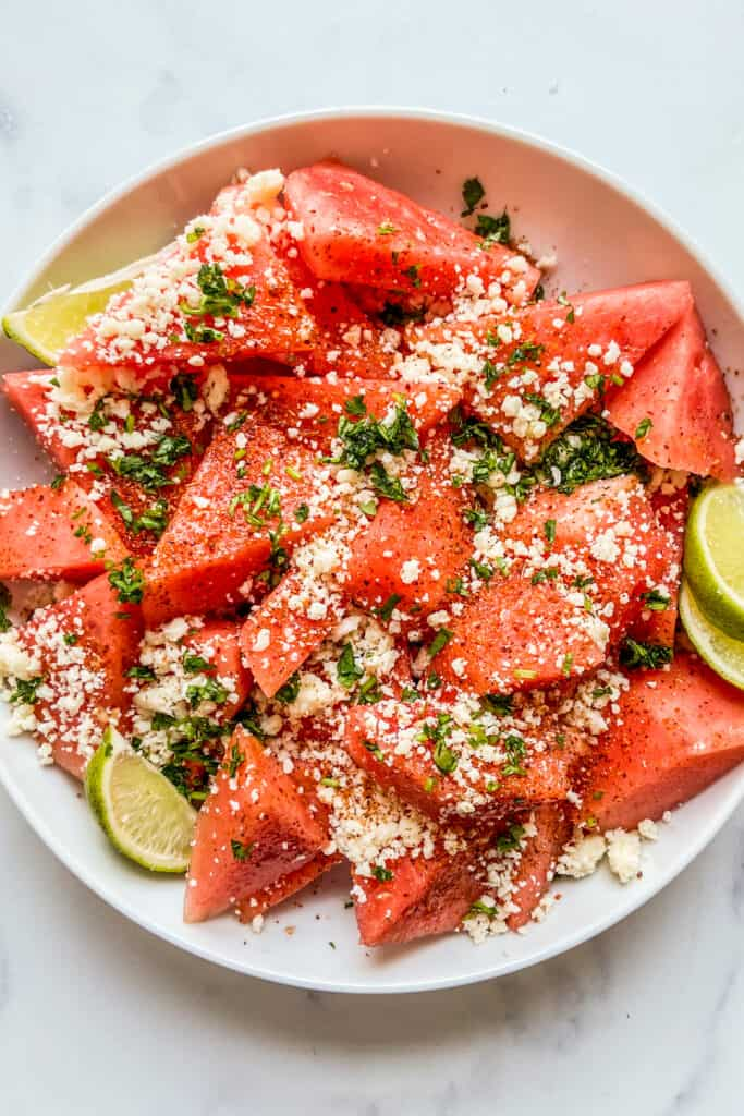 Sliced watermelon topped with cotija, tajin, and cilantro in a large white serving bowl.
