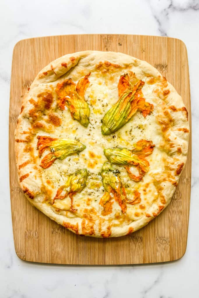 An overhead shot of zucchini flower pizza on a cutting board.