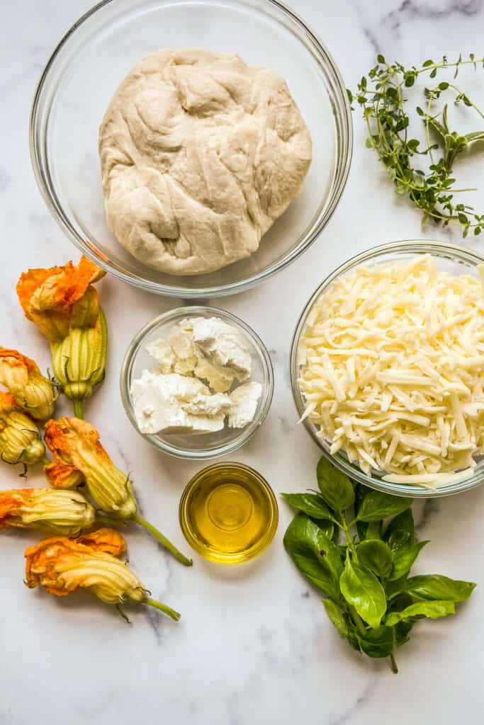 Pizza dough, shredded mozzarella, goat cheese, fresh herbs, zucchini flowers, and olive oil on a marble background.