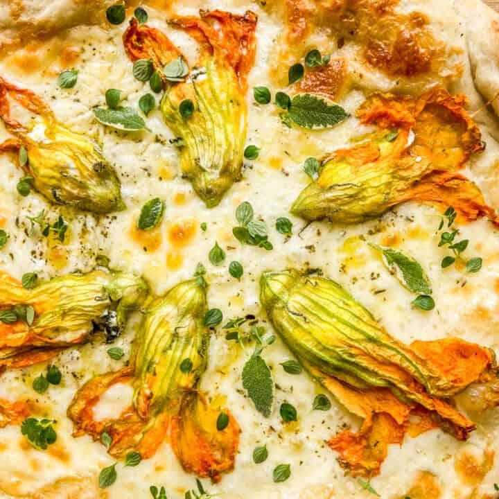 A closeup shot of a zucchini blossom pizza.