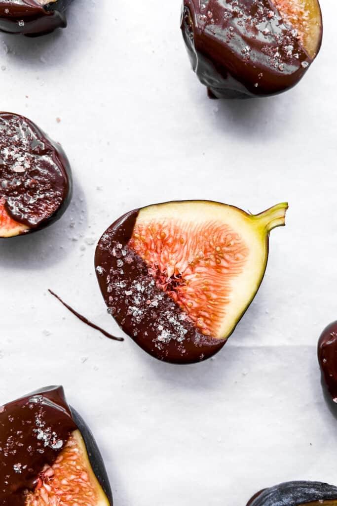 A closeup shot of dark chocolate dipped figs.