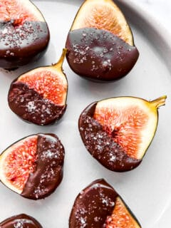 A closeup of dark chocolate dipped figs on a plate.