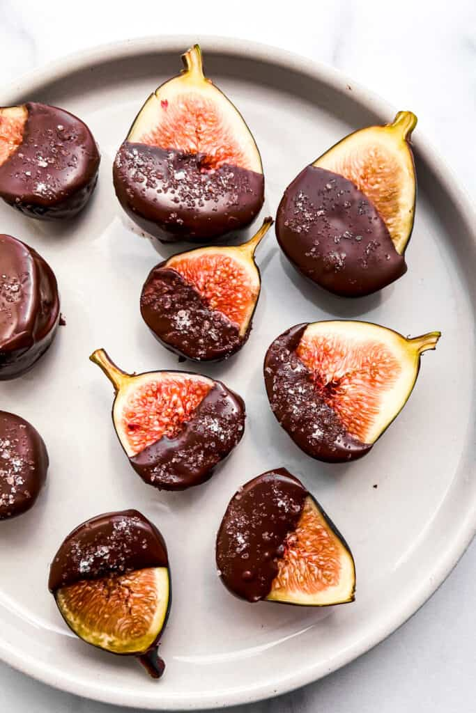 Figs covered in dark chocolate and salt on a small plate.