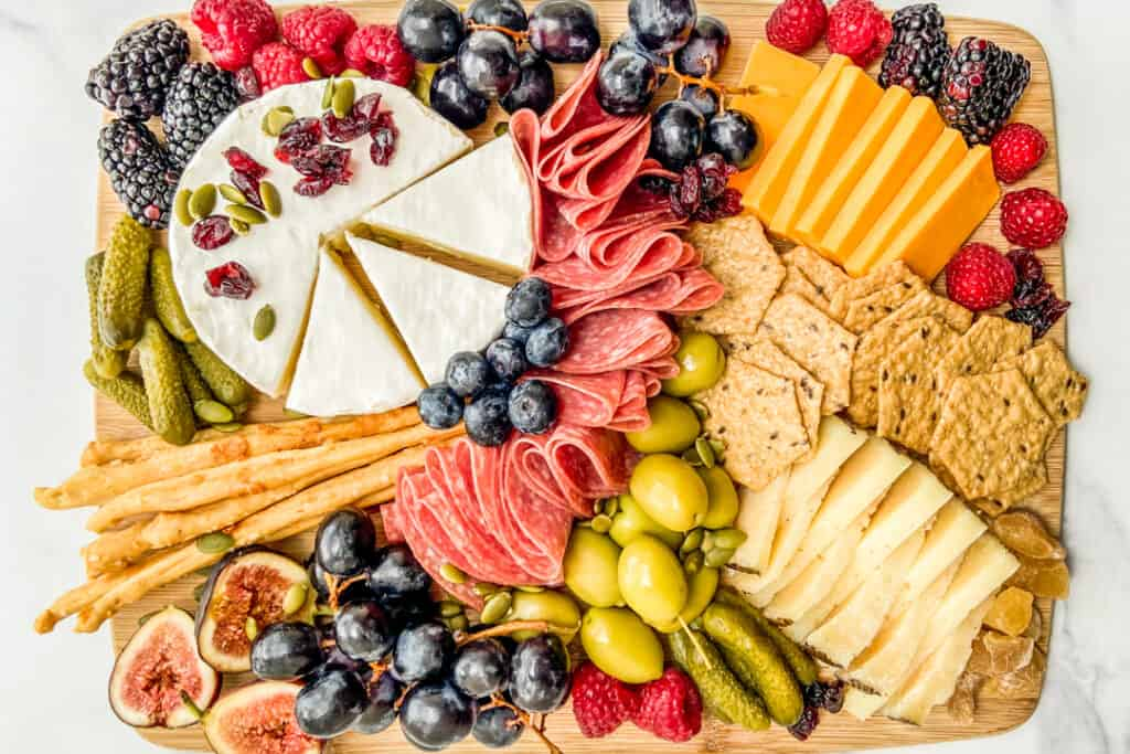 A charcuterie board with meat, cheese, fruit, olives, and nuts.