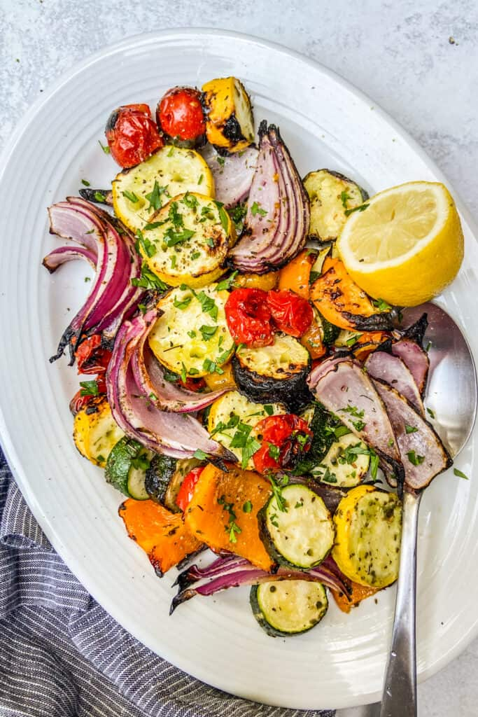 An overhead shot of a platter of grilled vegetables, topped with finely chopped herbs, next to a blue napkin.