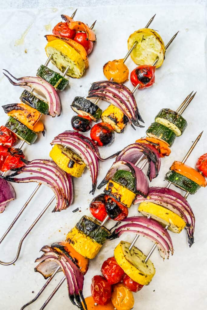 Grilled vegetables on metal skewers after coming off the grill.