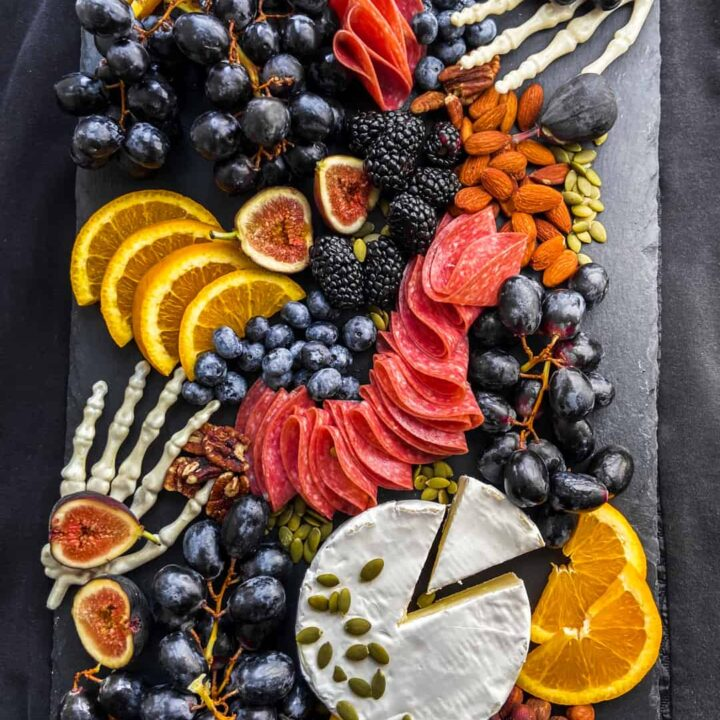 An overhead shot of a halloween charcuterie board on top of black fabric.