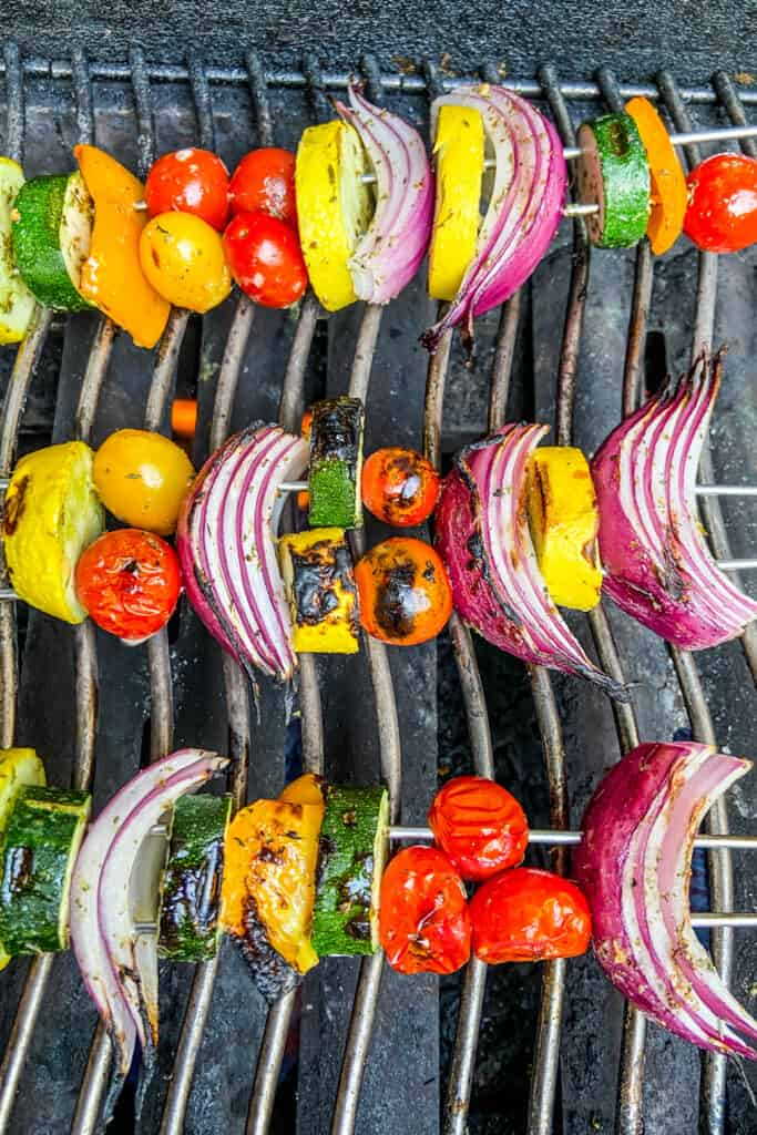 Char grilled veggies on skewers on a grill.