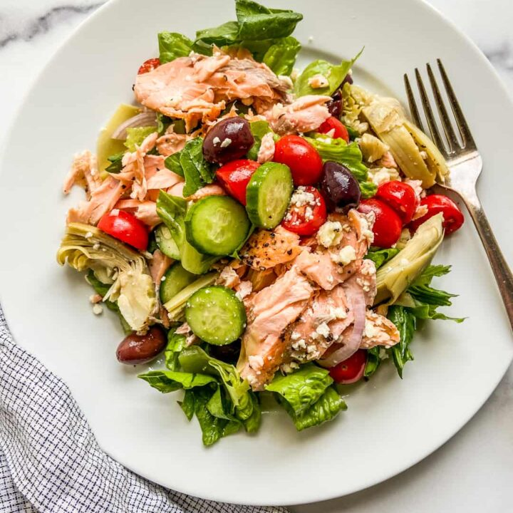 A large white plate with a Mediterranean salmon salad.
