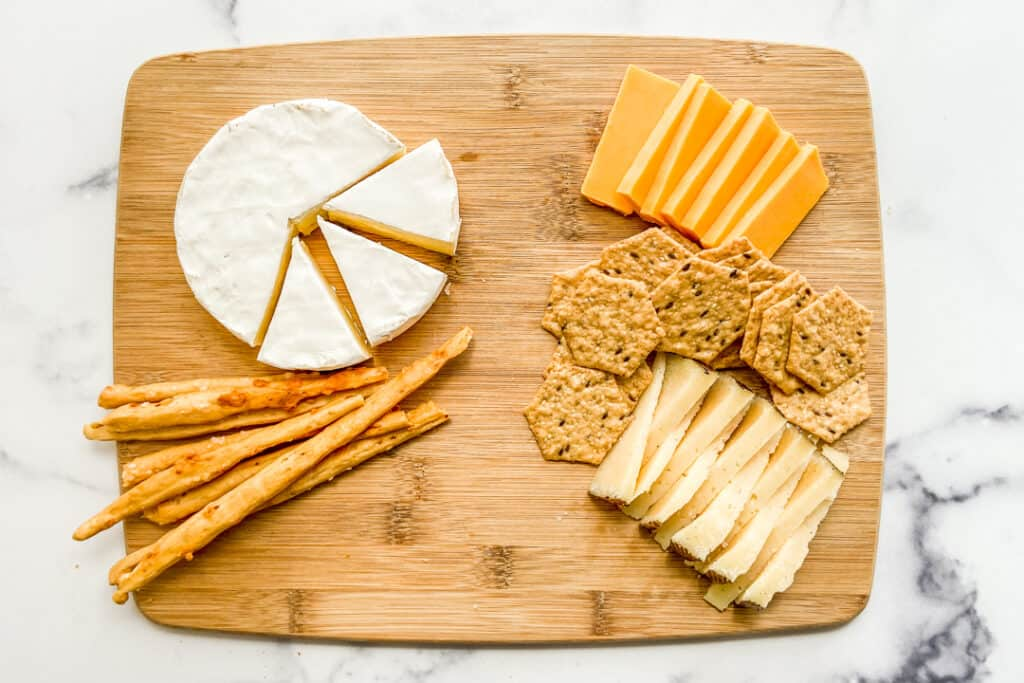 Cheese and crackers on a wooden board.