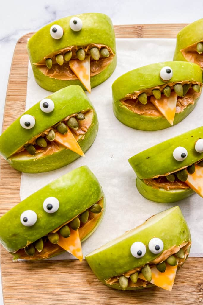Apples slices with candy eyes, cheese tongues, and pumpkin seed teeth on a cutting board.