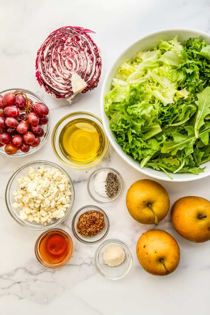 A bowl of lettuce, Asian pears, blue cheese, a half a radicchio, olive oil, grapes, salt and pepper, sugar, mustard, and red wine vinegar.