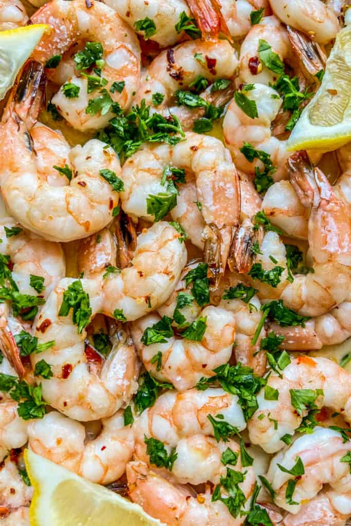 A closeup shot of baked shrimp topped with parsley.