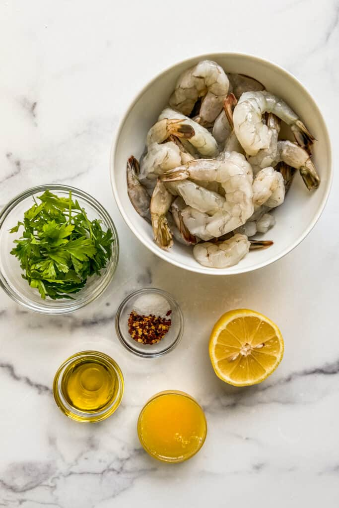Shrimp, parsley, red pepper flakes, olive oil, and a sliced lemon on a marble backdrop.
