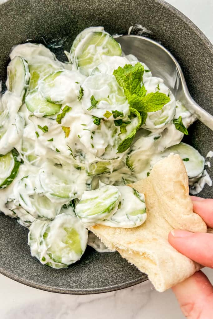 A closeup shot of a piece of pita bread scooping up cucumber yogurt salad.