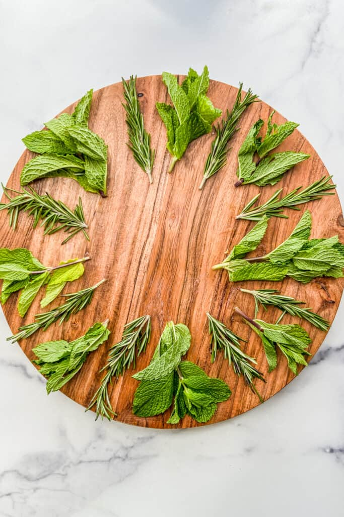 Fresh herbs on a large wooden plate.