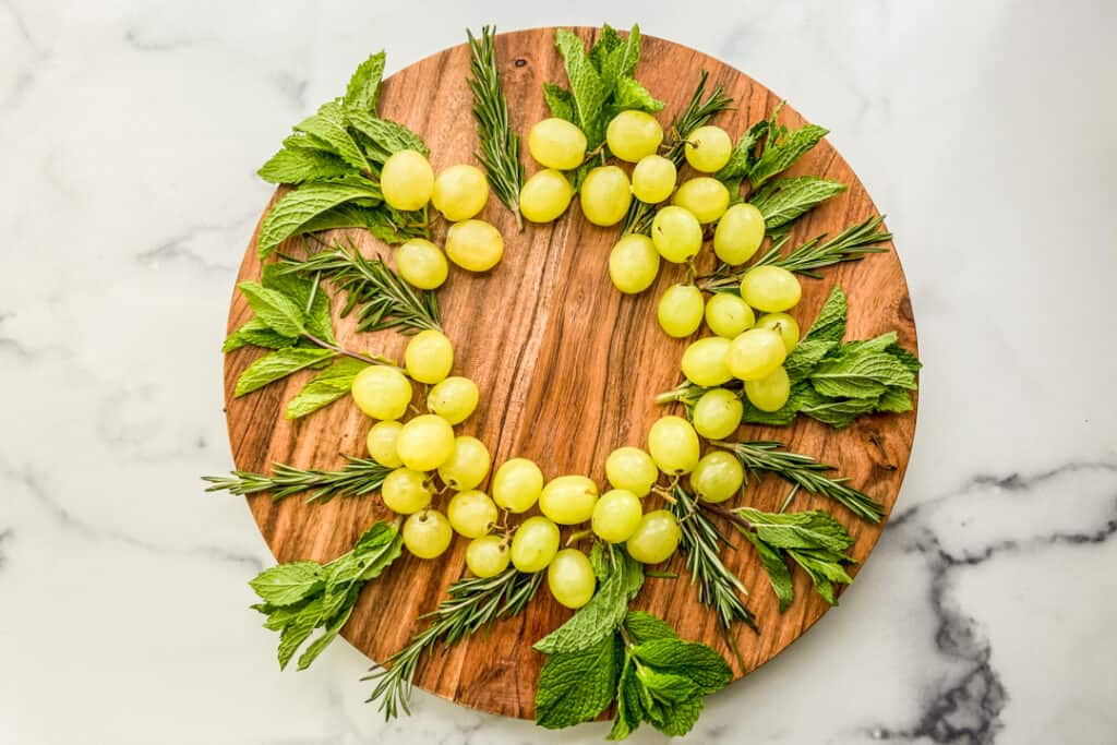 Fresh herbs and green grapes on a large wooden plate.