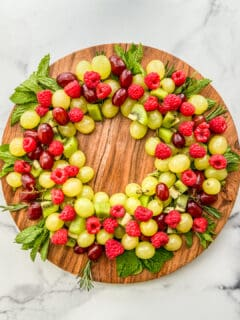 An overhead shot of a Christmas fruit wreath on a large wooden circular plate.
