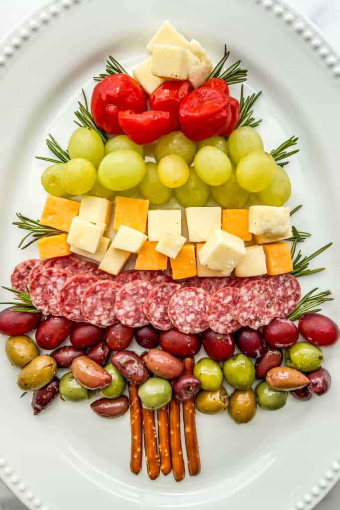 An overhead shot of a Christmas tree made out of cheese, fruit, and salami on a large white platter.