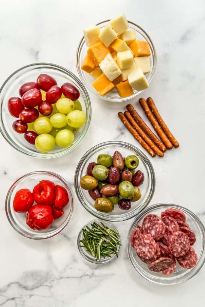 Grapes, cheese, pretzel, olives, salami, and rosemary.