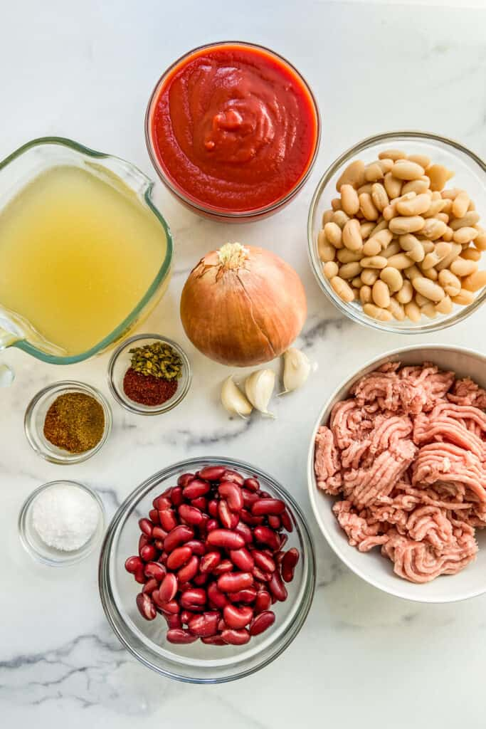 Ingredients for turkey chili - including beans, ground turkey, onion, tomato sauce, garlic, and spices on a marble background.