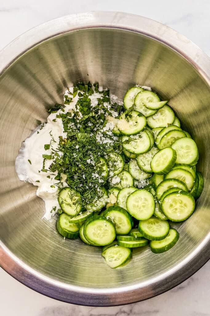 Sliced cucumbers, Greek yogurt, herbs, and sea salt in a large, metal mixing bowl.