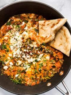 An overhead shot of a large skillet with menemen and slices of pita bread.
